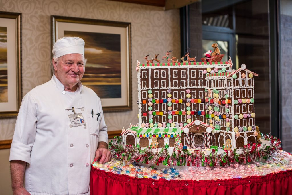 Pastry Chef Michael Fountain stands next to the gingerbread replica of the Cavalier Hotel. Credit: Westminster-Canterbury on Chesapeake Bay in Virginia Beach, Virginia.